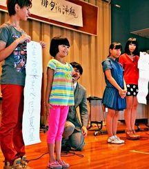 「俳句in沖縄」の俳句ボクシングで、自作の句を舞台で発表する子どもたち=30日、与那原町コミュニティーセンター