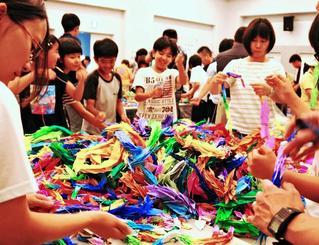 平和を願う千羽鶴を再生紙にするために仕分ける子どもたち=9日、糸満市摩文仁の県平和祈念資料館