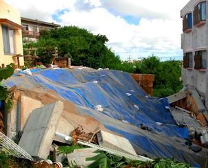土砂とともに民家(左)のブロック塀が崩落し、隣接するアパート(右)に流れ込んだ=29日、うるま市石川東恩納