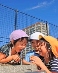 青空の下で遊び回り、乾いたのどを潤す園児たち=18日午後、豊見城市・豊崎にじ公園(松田興平撮影)