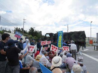 米軍関係車両が出るのを止めようと座り込む市民ら=7日午前10時頃、名護市辺野古米軍キャンプ・シュワブゲート前