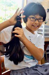 切った髪を手にする城間帆波さん=3日、宜野湾市嘉数