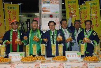 フルーツシークヮーサーをPRする大城常務理事(左から3人目)ら=16日、浦添市・県中央卸売市場