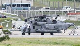 米軍普天間飛行場のCH53E大型輸送ヘリ。窓のない部分をシートで覆う作業員=13日午前11時52分、宜野湾市
