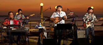 夕日を背景に歌うBEGINのメンバー=石垣島ビーチホテルサンシャイン(同実行委員会提供)