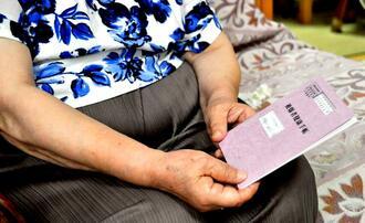 2月に初めて取得した真新しい被爆者健康手帳を手に、自分や家族を苦しめた原爆への思いを語る女性=宜野湾市内(画像の一部を加工しています)
