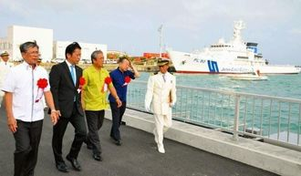 尖閣領海警備の専従体制完成披露式後、新たに完成した桟橋を渡り巡視船に向かう関係者ら=16日、石垣市浜崎町