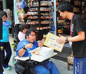 国際通りの「古酒家」で、梅田昌和店長(右)に、コミュニケーション支援ボードの活用を求める仲盛雄二さん(中央)=26日午後、那覇市久茂地・国際通り