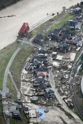 豪雨で球磨川(上)が氾濫し、被害を受けた熊本県球磨村の住宅地。川に架かる橋は流された=10日午前9時40分(共同通信社ヘリから)