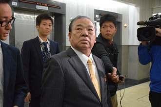報道陣の取材を受ける安慶田光男副知事(中央)=20日午前8時44分、県庁