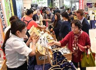 久米島の特産品を買い求める来場者でにぎわう即売会場=7日午前、那覇市久茂地・タイムスビル