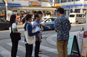 市の職員から看板設置について指摘を受ける事業者=13日、那覇市の国際通り