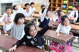 先生の質問に、元気よく手をあげる天妃小の児童たち=9日午前、那覇市久米