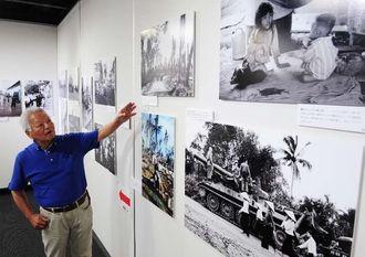 自身が撮影した写真の前で時代背景などを語る石川文洋さん=15日午後、那覇市久茂地・タイムスギャラリー