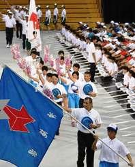 デンファレの花を振り、入場行進する県選手団=28日午前10時17分、山形県総合運動公園総合体育館