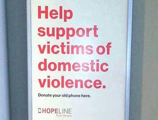 「DV 被害者をサポートしよう」と、資金集めのための携帯電話の寄付を呼び掛ける箱。携帯電話会社の店内に設置されている