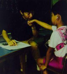 先生が口から吐き出す息の強弱を手で感じ取って、発音の練習をしているところ。