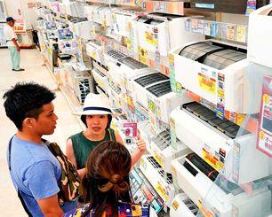 エアコンの品定めをする買い物客=5日、那覇市・エディオン那覇メインプレイス店(画像の一部を加工しています)