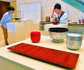 器や万華鏡など個性的な作品が並ぶうるし組展=14日午後、那覇市久茂地・タイムスビル1階エントランス