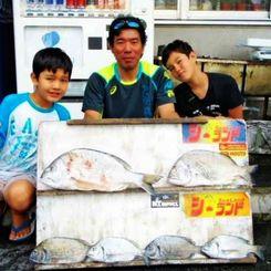 泡瀬海岸で50.5センチ、2.11キロのチンシラーを釣った喜屋武正憲さん(中)=12日