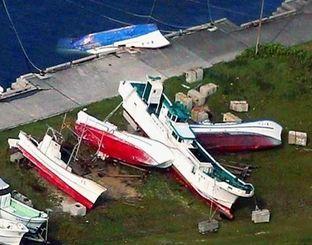 台風21号の影響で陸揚げされた漁船が横倒しに。1隻は転覆した=29日午前8時57分、与那国町・久部良漁港(石垣海上保安部提供)
