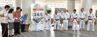 「第1回沖縄空手国際大会」に向け、残暦板の除幕を行う実行委員ら=1日、県庁の県民ホール