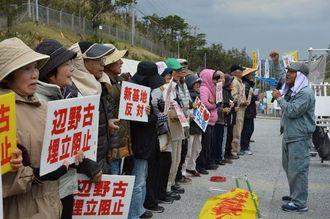 ゲート前で「沖縄を返せ」を歌う集会参加者=22日、名護市の米軍キャンプ・シュワブのゲート前