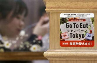 飲食店の店頭に貼られた「Go To イート」のプレミアム付き食事券が使えることを伝えるステッカー=11月、東京都足立区