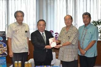 安慶田光男副知事(左から2人目)に協賛金目録を贈る嘉手苅義男社長(同3人目)=21日、県庁