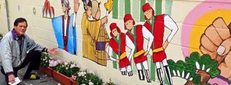 民家の塀に「豊年踊」の演目などが描かれ、喜ぶ仲井間宗徳区長=名護市仲尾次
