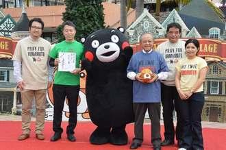 熊本地震への支援で「くまモン」からお礼を受ける野国町長(右から3人目)ら関係者=11日、北谷町美浜