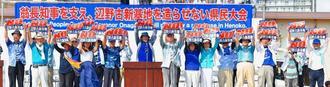 「NO 辺野古新基地」のボードを掲げる登壇者=12日午後3時すぎ、那覇市・奥武山陸上競技場
