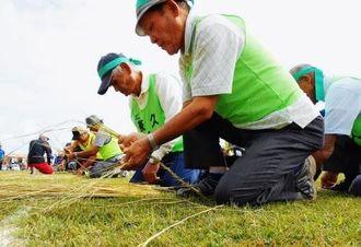 熟練の技が光った年齢別の「縄ない競争」=宜野座村立松田小学校グラウンド