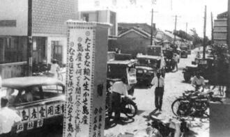 ジープによるパレードや立て看板で島産品愛用を訴えた=1960年、石垣市(県工業連合会提供)