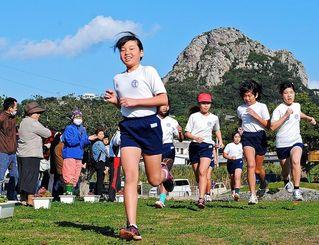 島のシンボル城山を背に、父母の声援を受けながら元気よく走り出す子どもたち=2月21日、伊江村