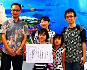 入園者8千万人目となった矢頭さん一家と片山所長(左)=4日、本部町・海洋博公園
