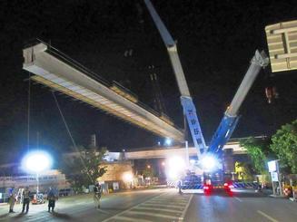 鋼橋をクレーンでつり上げて、架設する作業=3月28日未明、浦添市前田(県提供)