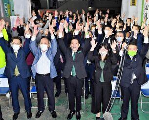 3期目の当選を確実にし、バンザイする松本哲治氏(中央)と支持者=7日午後11時8分、浦添市伊祖の選挙事務所