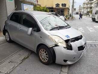 銀行に突っ込み、バックして道路向かいの建物にぶつかって停車した乗用車=9日午後1時ごろ、那覇市曙