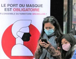 11日、ベルギー・ブリュッセルで「マスク着用は義務」と呼び掛ける看板の前に立つ女性と子供(共同)