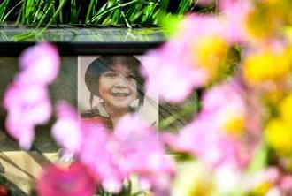 レェ・ティ・ニャット・リンさんの遺体が遺棄された現場付近に供えられた花と遺影=24日午前、千葉県我孫子市