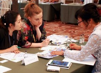 海外のバイヤー(中央)に商品をPRする出展企業の担当者(右)=4日、沖縄かりゆしアーバンリゾート・ナハ