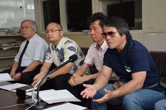 国へ損害賠償請求した経緯を話す原告の目取真俊さん(右)=12日午後、県庁記者クラブ