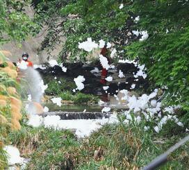 風が吹き泡消火剤が舞う中、消火剤除去のために放水する消防隊員(左奥)=4月11日、宜野湾市・宇地泊川