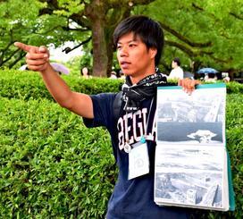 写真を使って原爆投下時の状況を説明する村上正晃さん=2日、広島市の原爆ドーム前