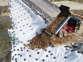 埋め立て区域に土砂を投入するダンプカー=14日、名護市辺野古(小型無人機で撮影)