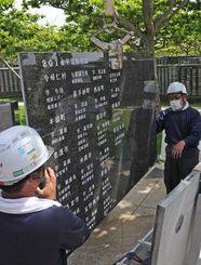 新たに追加された沖縄戦関連戦没者の刻銘板を取り付ける作業員=17日午前、糸満市摩文仁・平和祈念公園