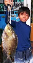 都屋漁港で38センチ、1キロのカーエーを釣った兼城光浩さん(写真は息子の龍光君)=24日
