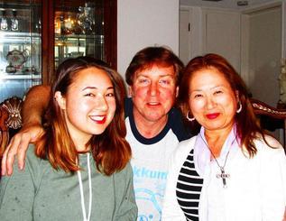 両親と一緒に笑顔を見せるエイプリル・ウツギニモさん(左)