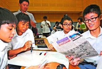 新聞記事を読んで、論点を深め合う生徒たち=1日、沖縄市・県立総合教育センター